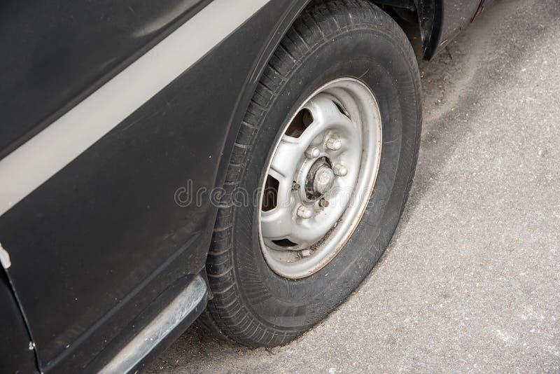 Gammal rostig skeppsbruten bil med ett punkterat gummihjul royaltyfria foton