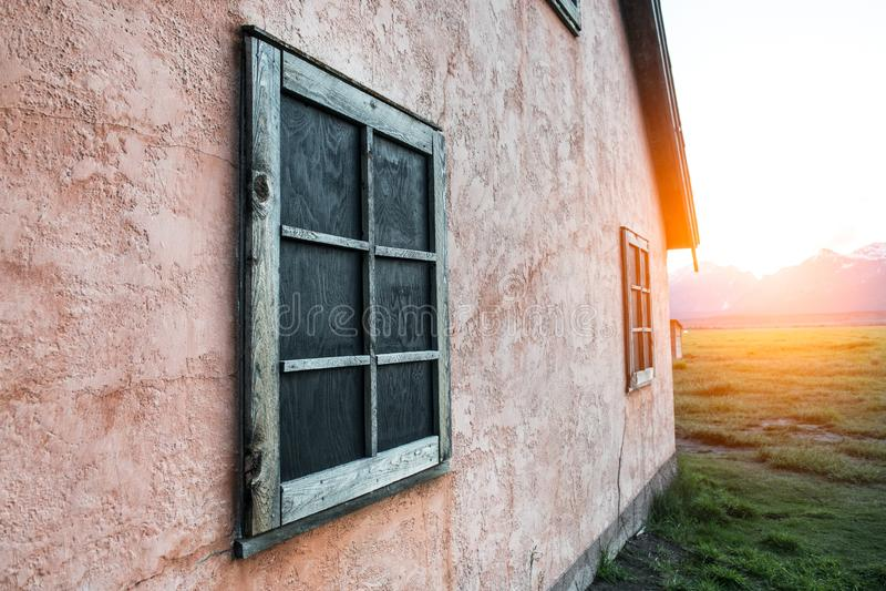 Gammal rostig träram på den sten målade rosa väggen på berghus på solnedgångtid royaltyfri bild