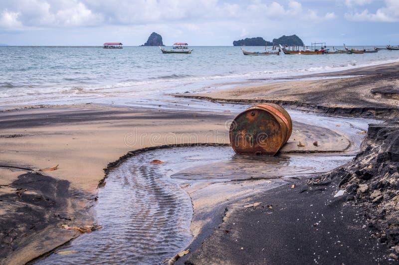 Gammal rostig trummaolja på stranden i Asien royaltyfri fotografi
