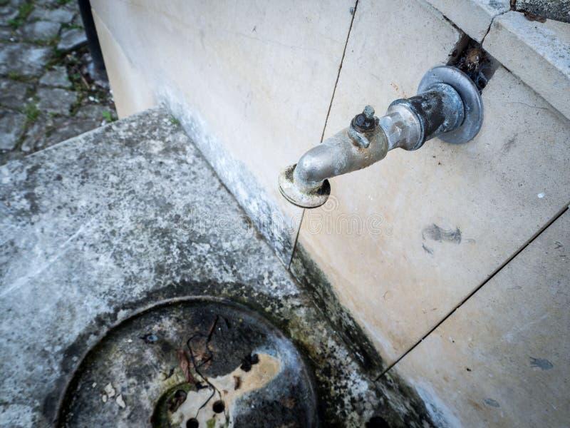 Gammal rostig vattenkran på den konkreta gråa väggen arkivfoton