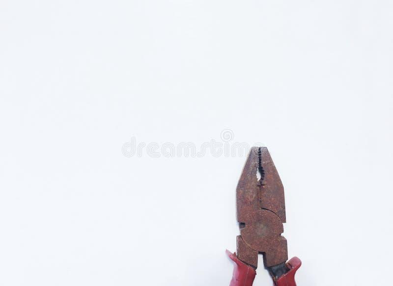 Gammal rostplattång med det röda handtaget som isoleras på vit bakgrund royaltyfria foton
