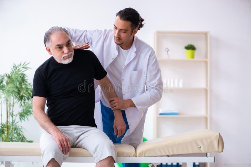 Gammal sårad man som besöker den unga doktorn arkivfoton