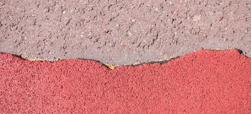 Gammal sönderriven röd gummismularäkning, trampkvarn eller körande bakgrund för textur för stadion för lekplats för spåryttersida royaltyfria bilder
