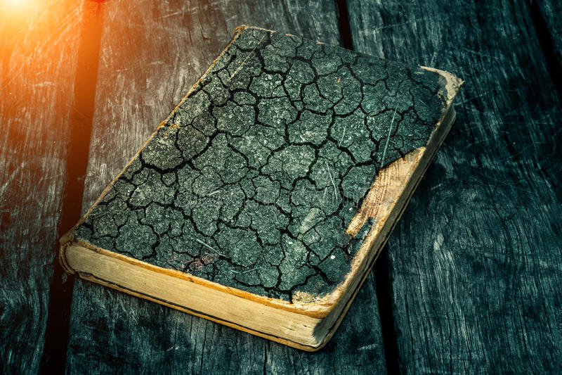 Gammal söndersliten bok på en trätabell Läsa vid levande ljus Tappningsammansättning forntida arkiv Antik litteratur royaltyfri foto