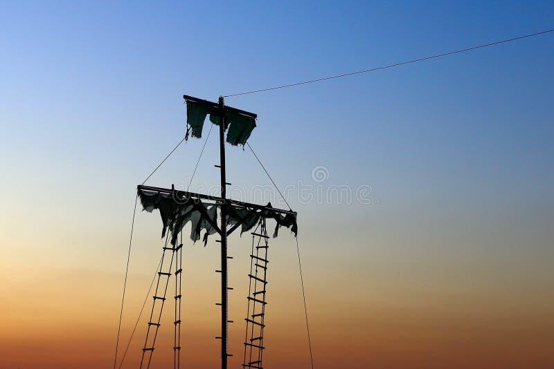 Gammal sailer piratkopierar skeppet, med sönderrivet seglar, på solnedgången fotografering för bildbyråer