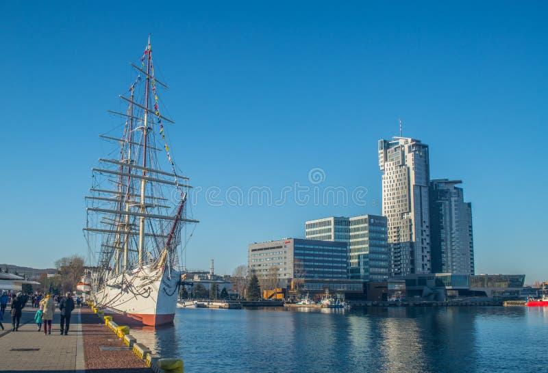 Gammal sailship i en hamn och moderna byggnader arkivfoton