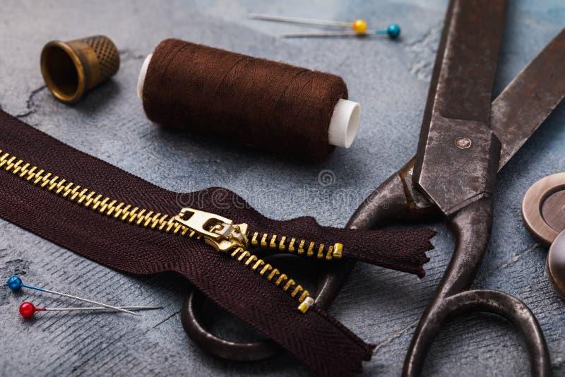 Gammal sax, blixtlås för kläder och andra hjälpmedel för att sy och mindre reparationer royaltyfri bild