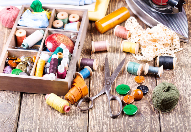 Gammal sax, olika trådar, järn och sömnadhjälpmedel arkivbild