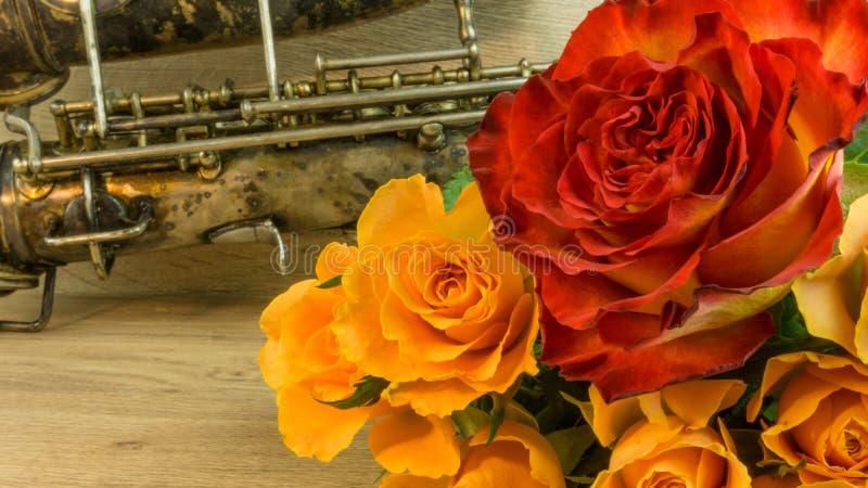 Gammal saxofon med rosor arkivfoto