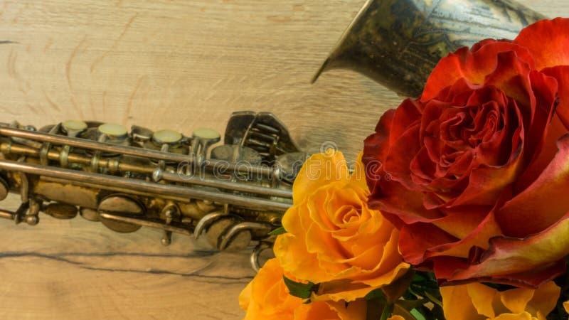 Gammal saxofon med rosor arkivbild