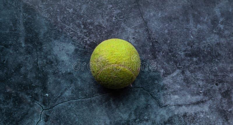 Gammal sjaskig och dammig gr?n tennisboll arkivbild