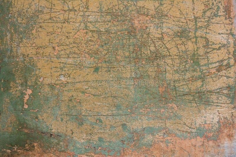 Gammal sjaskig rosa gul betongvägg med sprickor, djupa skrapor och fläckar av grön målarfärg och smuts Textur f?r grov yttersida royaltyfri foto