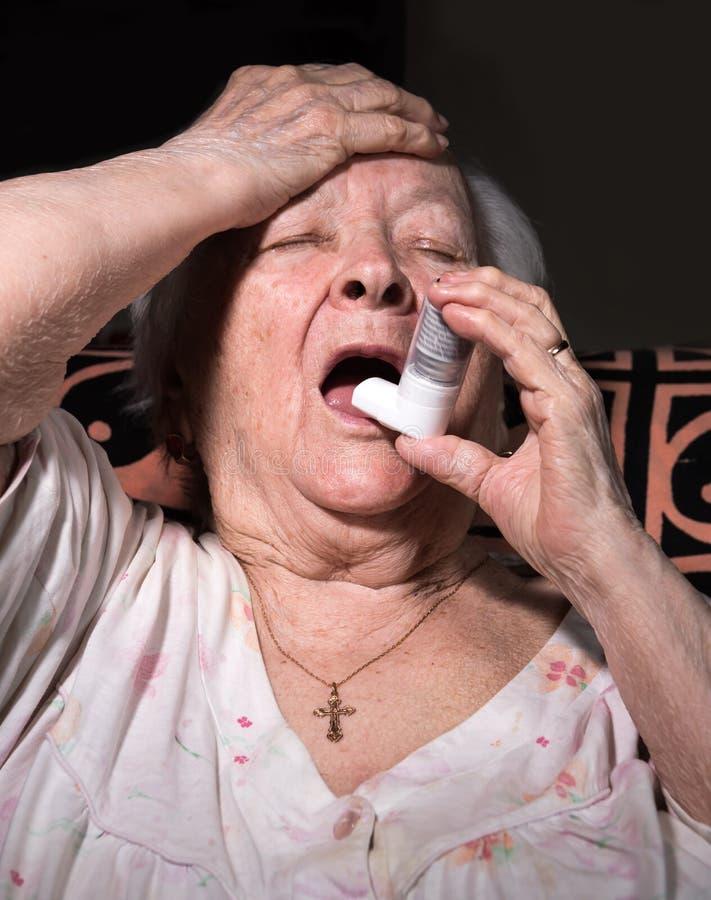 Gammal sjuk kvinna med astmainhalatorn royaltyfria bilder
