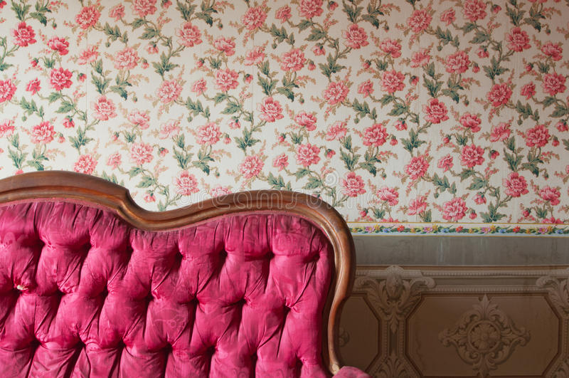Gammal skadad röd soffa i ett antikt hus. Blommatapet i väggen royaltyfria foton