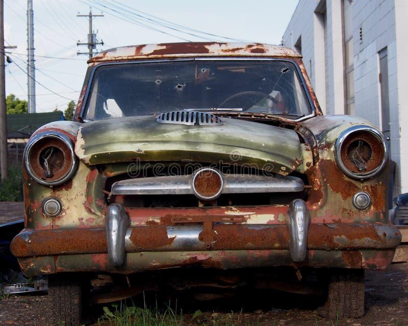 Gammal skeppsbruten bil med kulhål i vindruta arkivfoto