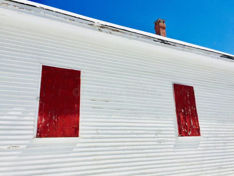 Gammal skolhus med lampglaset och röda fönsterslutare royaltyfria foton