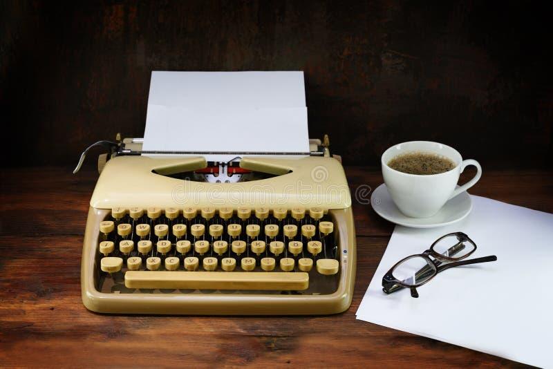 Gammal skrivmaskin från femtiotalet med papper, kaffe och exponeringsglas på en mörk lantlig trätabell, utvald fokus, smalt djup  arkivbilder