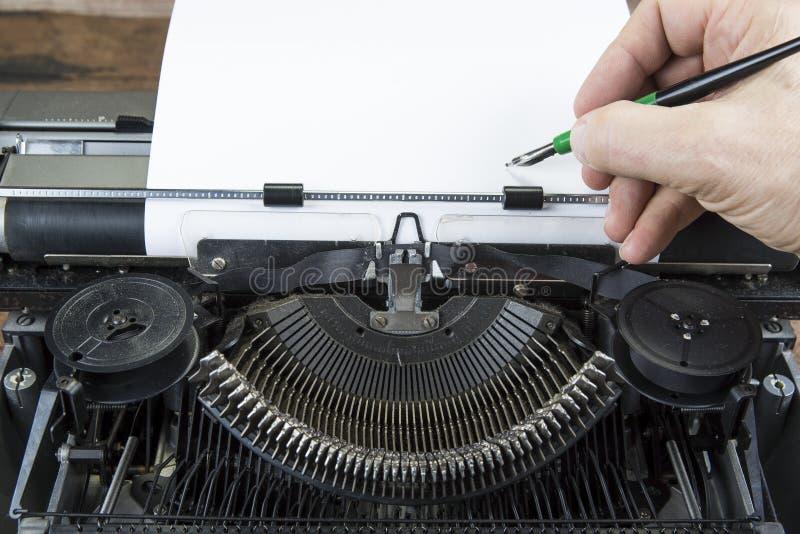 Gammal skrivmaskin från seventies med pappers- och kopieringsutrymme Med handstilhanden royaltyfri fotografi
