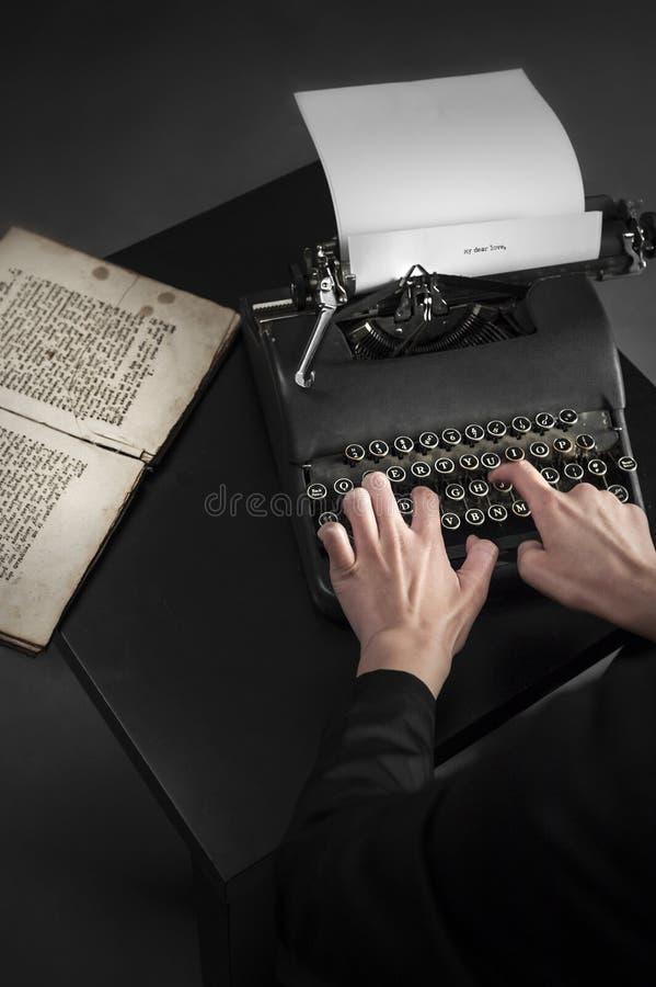 Gammal skrivmaskin och ett forntida manuskript royaltyfria foton