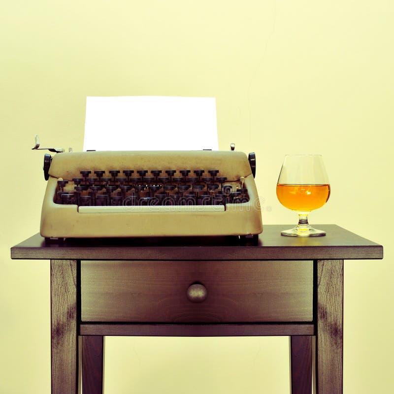 Gammal skrivmaskin och starksprit arkivbild