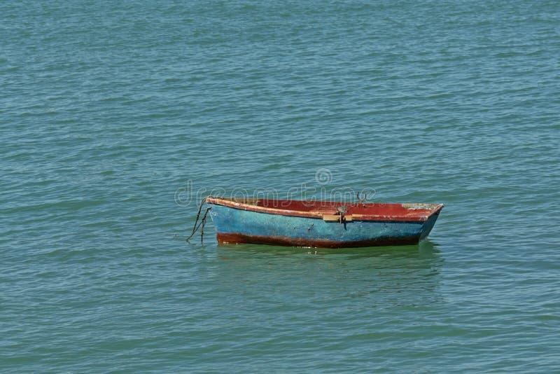 Gammal sliten blå och röd jolle i havet royaltyfria bilder
