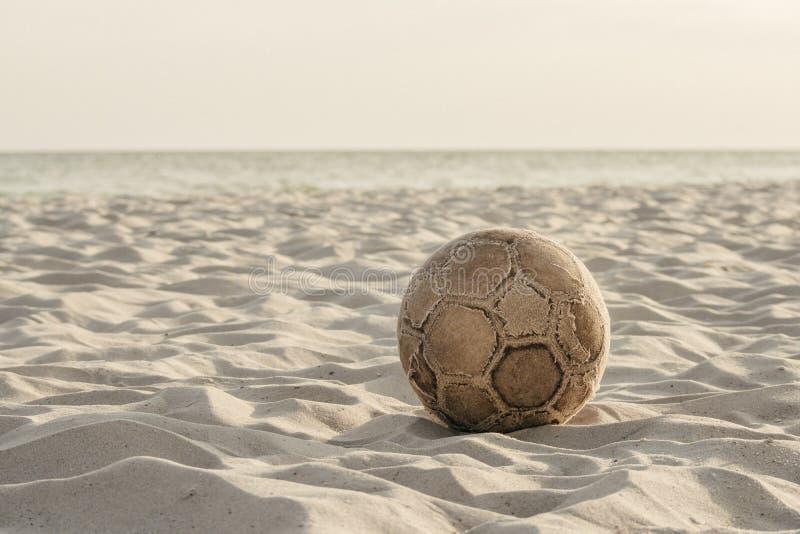 Gammal sliten fotbollboll på stranden fotografering för bildbyråer