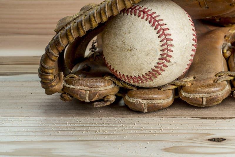 Gammal sliten läderbaseballhandske och använd boll på ett trä royaltyfria bilder
