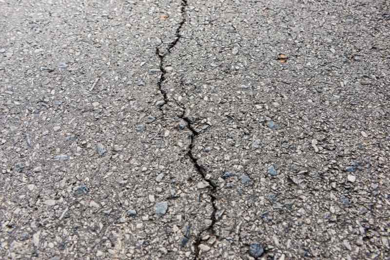 Gammal sliten och sprucken asfalt med sprickor arkivfoto