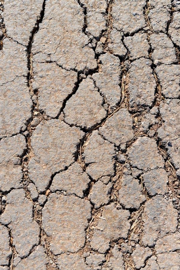 Gammal sliten och sprucken asfalt med sprickor fotografering för bildbyråer