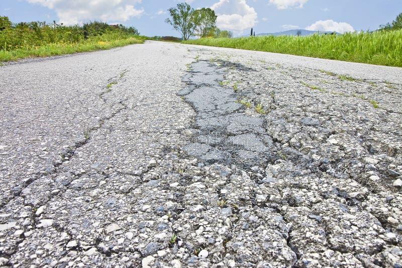 Gammal sliten och sprucken skadad bakgrund för asfaltvägyttersida royaltyfri fotografi