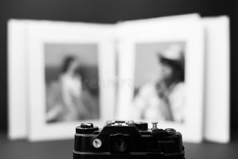 Gammal SLR kamera på öppnad bakgrund för fotoalbum royaltyfri bild