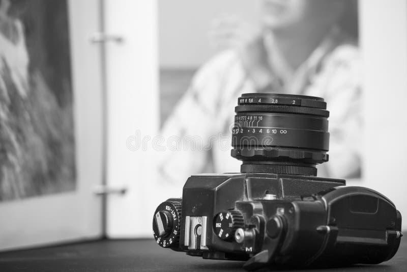 Gammal SLR kamera på öppnad bakgrund för fotoalbum arkivfoto