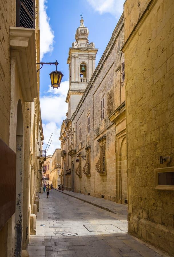 Gammal smal gata av Mdina med det Carmelite kyrkliga Klocka tornet - Mdina, Malta arkivfoto