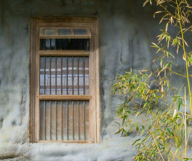 Gammal smutsig fönsterram med arreststänger i en stenvägg royaltyfri fotografi