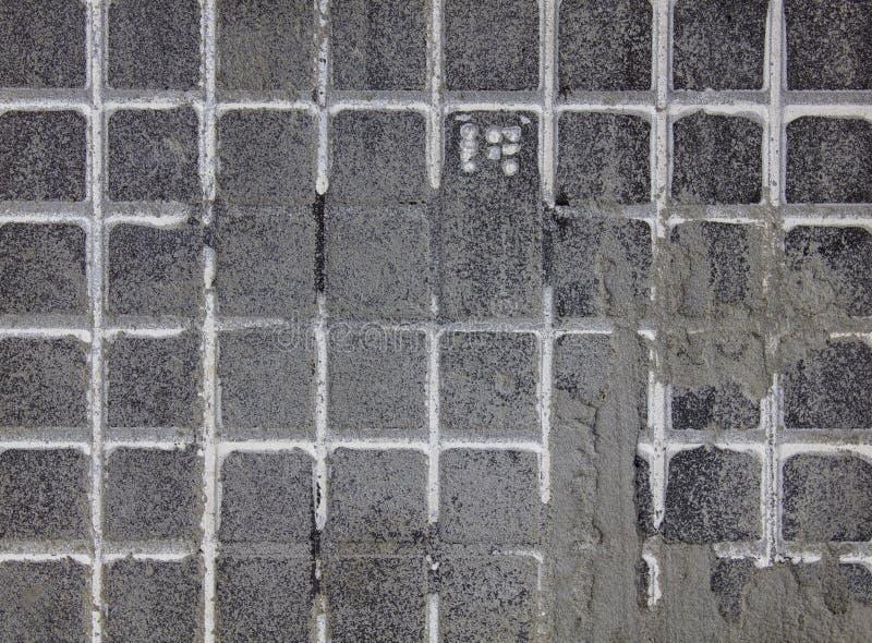 Gammal smutsig svart grå vägg med vita rutiga modelllinjer och cementfläckar Textur f?r grov yttersida royaltyfri bild