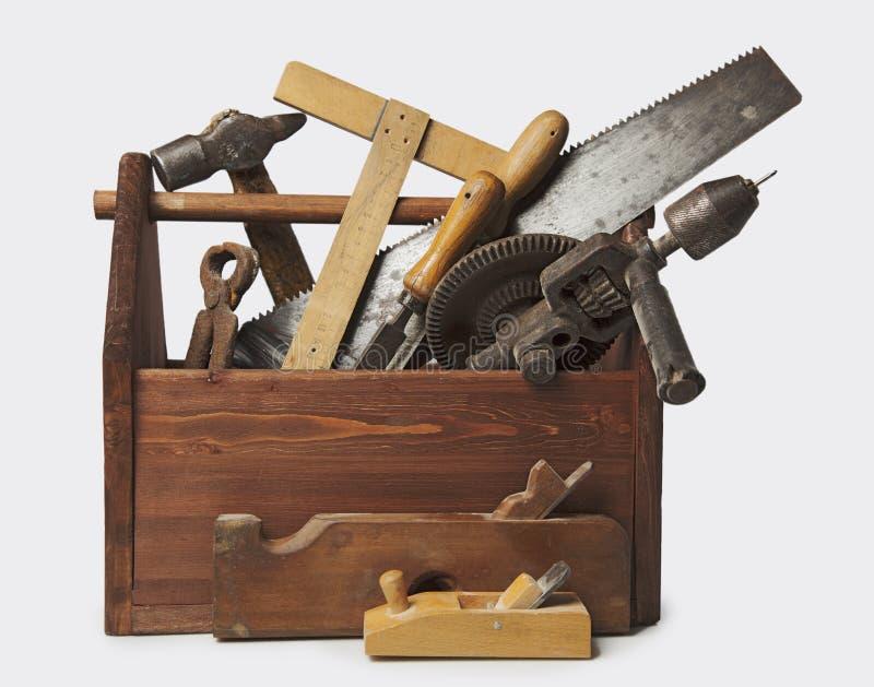 Gammal snickareWooden toolbox med hjälpmedel som isoleras på vit royaltyfri foto