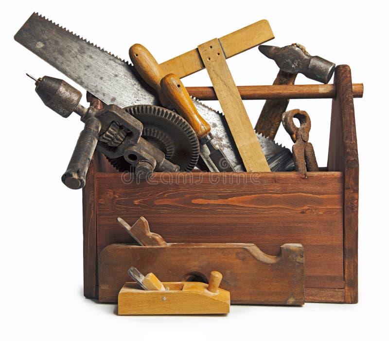 Gammal snickareWooden toolbox med hjälpmedel som isoleras på vit fotografering för bildbyråer