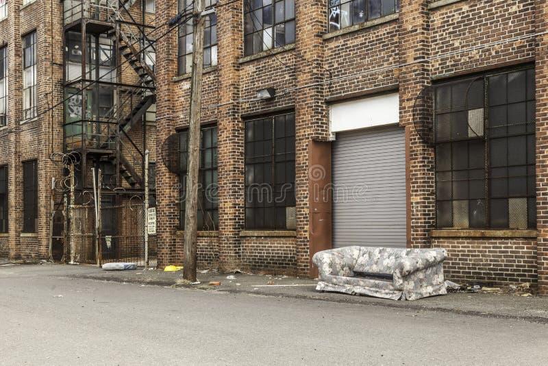 Gammal soffa framme av Abandoned byggnad arkivfoto