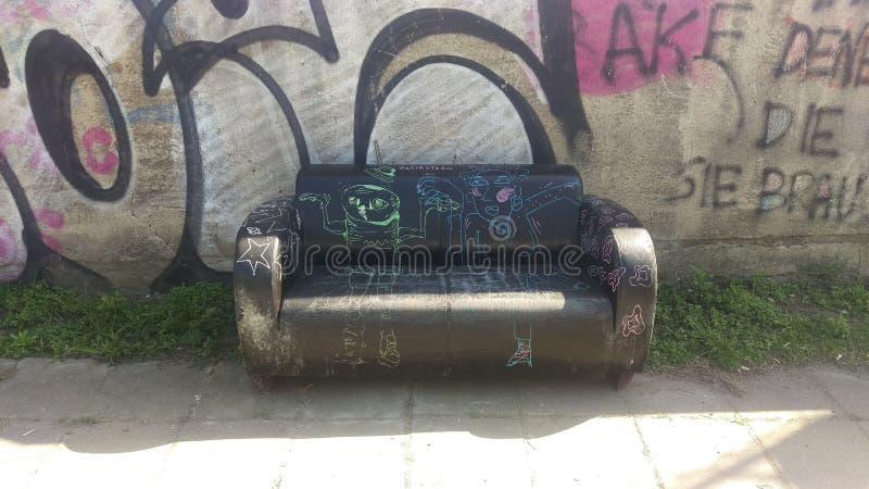 Gammal soffa framme av graffityväggen arkivbilder