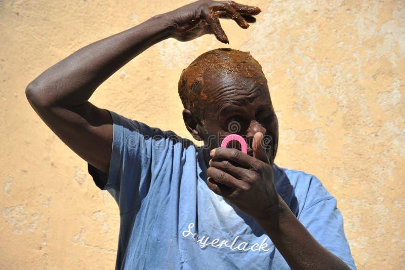 Gammal somalisk färg hans hår med henna royaltyfria foton