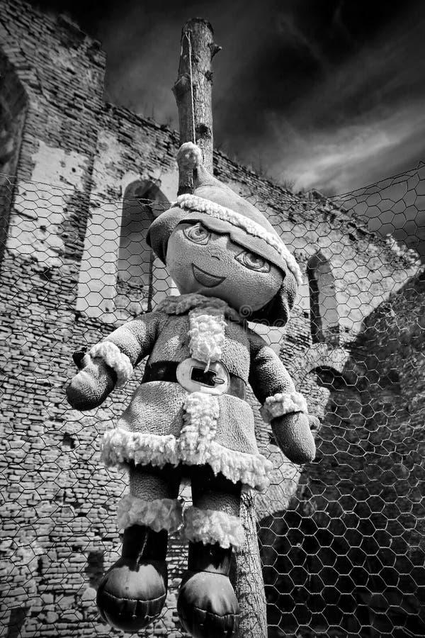 Gammal spöklik docka som hänger på ett staket royaltyfria foton