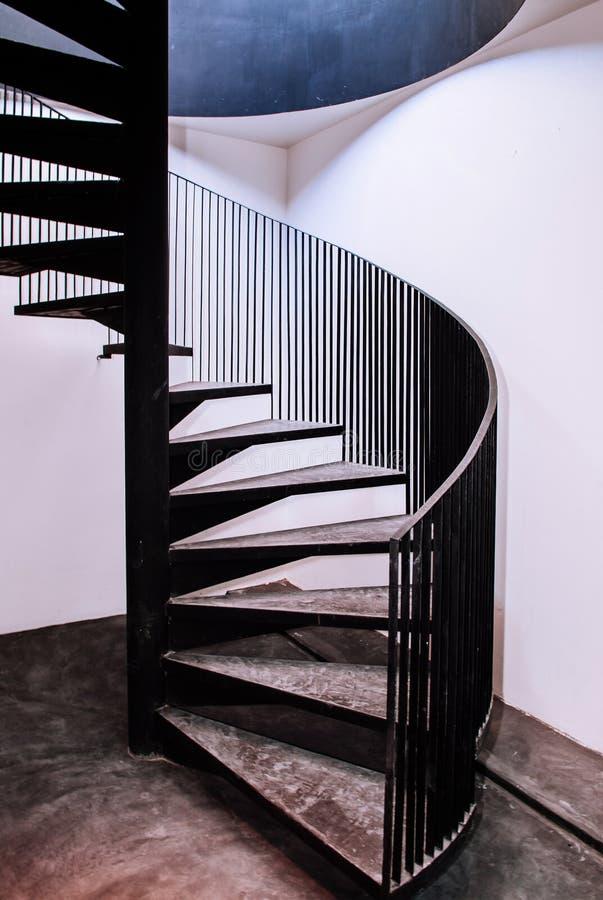 Gammal spiral trappa för industriell vind med det konkreta golvet, svart meta fotografering för bildbyråer