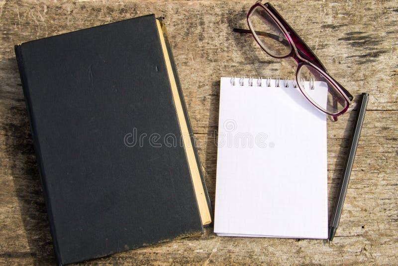 Gammal stängd bok, exponeringsglas, notepad och penna på träbakgrund royaltyfri bild