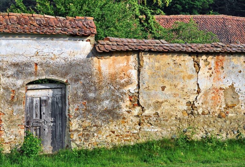 Gammal stärkt vägg med den wood dörren arkivfoton