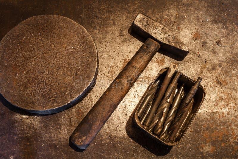 Gammal stålhammare med trähandtaget, den tunga cirkeln för järn och drillborrbitar för metall i asken på metallbakgrunden royaltyfria foton