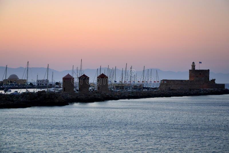 Gammal stad av Rhodos medan rosa solnedgång, lugna hav, grekisk monument och hamnsikt Värme färger, dimmig bakgrund Rhodos Grekla royaltyfria bilder