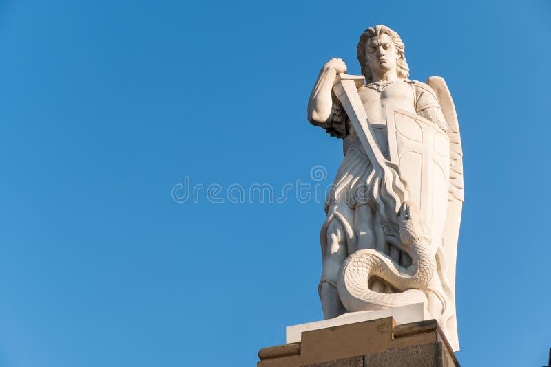 Gammal staty av ärkeängeln St Michael som slåss draken royaltyfri bild