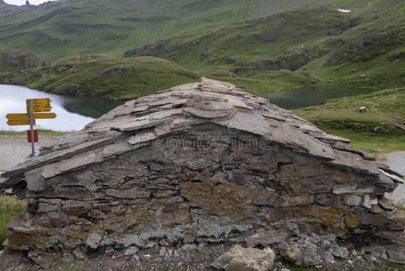 gammal stenchalet på kusten av en liten sjö i de alpina bergen grindelwald switzerland royaltyfri foto