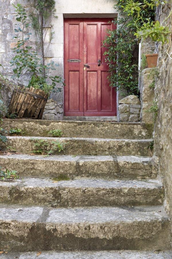 Gammal stentrappa med ingångsdörren arkivbilder