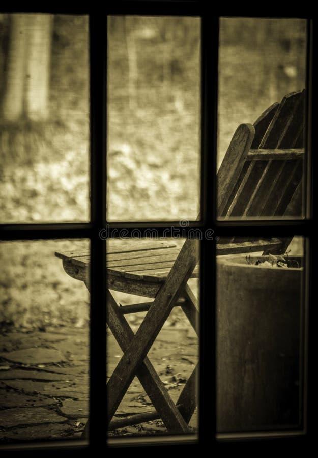 Gammal stol till och med fönstret fotografering för bildbyråer